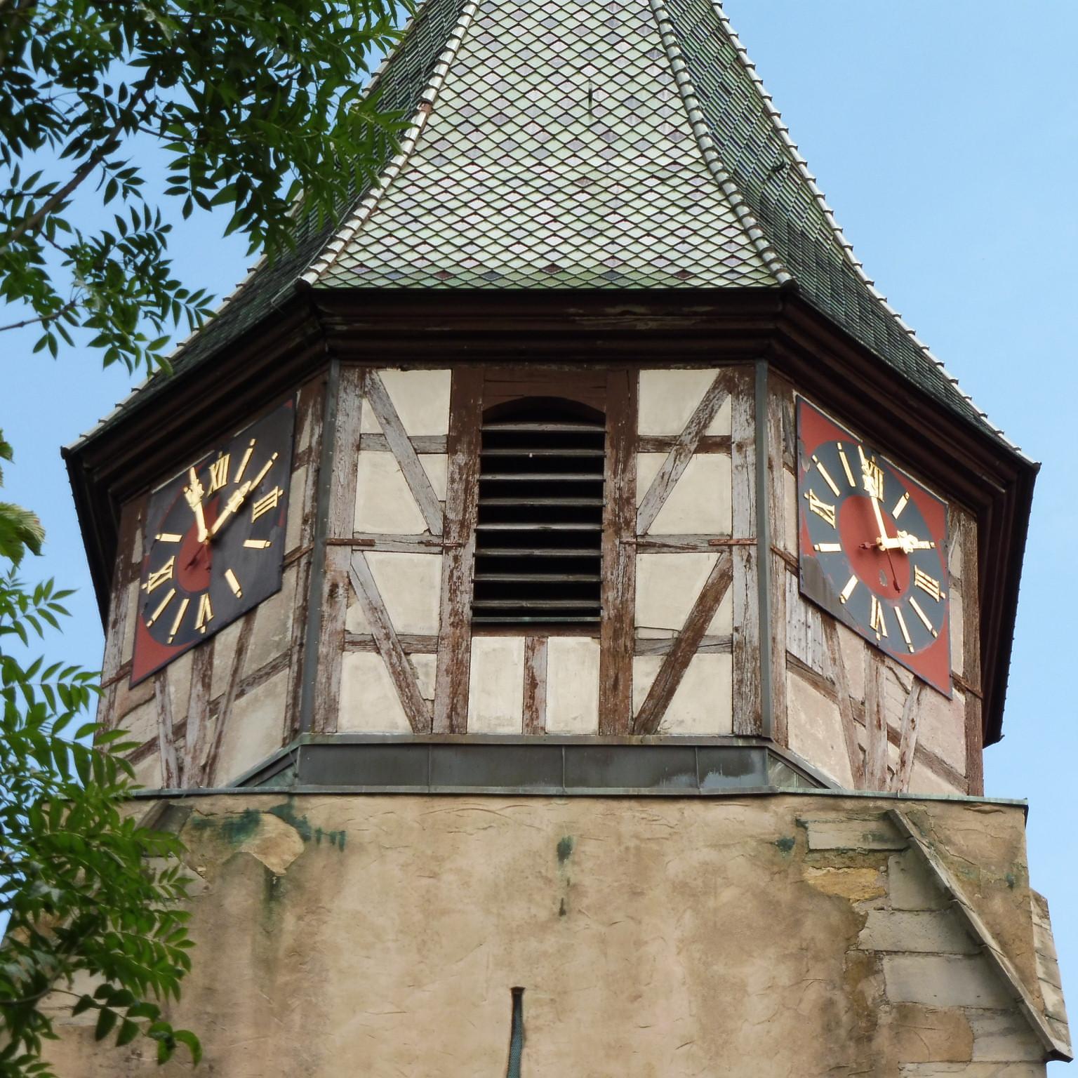 Fachwerkaufsatz des Turms: Oberflächenschäden an den Zifferblättern und in der Fassade sichtbar gewordene ausgewaschene Kupfersalze